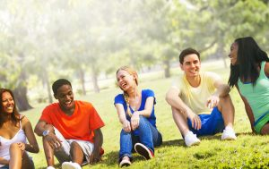 Diverse group of teens laughing together in the park