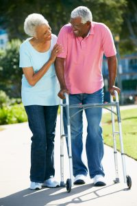 Elderly African American couple walking slowly in the park